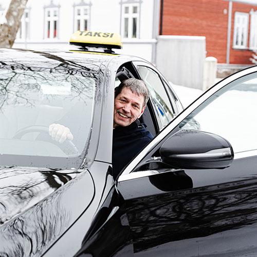 Smiling Taksimestari driver in a car