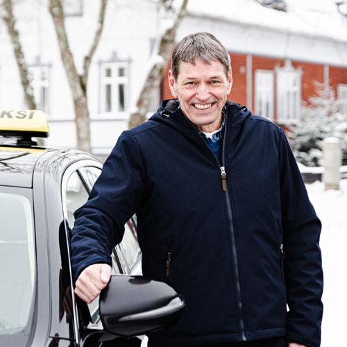 Hymyilevä Taksimestari-kuljettaja auton vieressä Raumalla